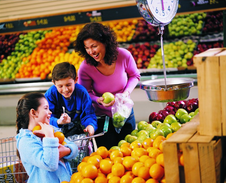 Mother and children shopping for fruit at the grocery store.