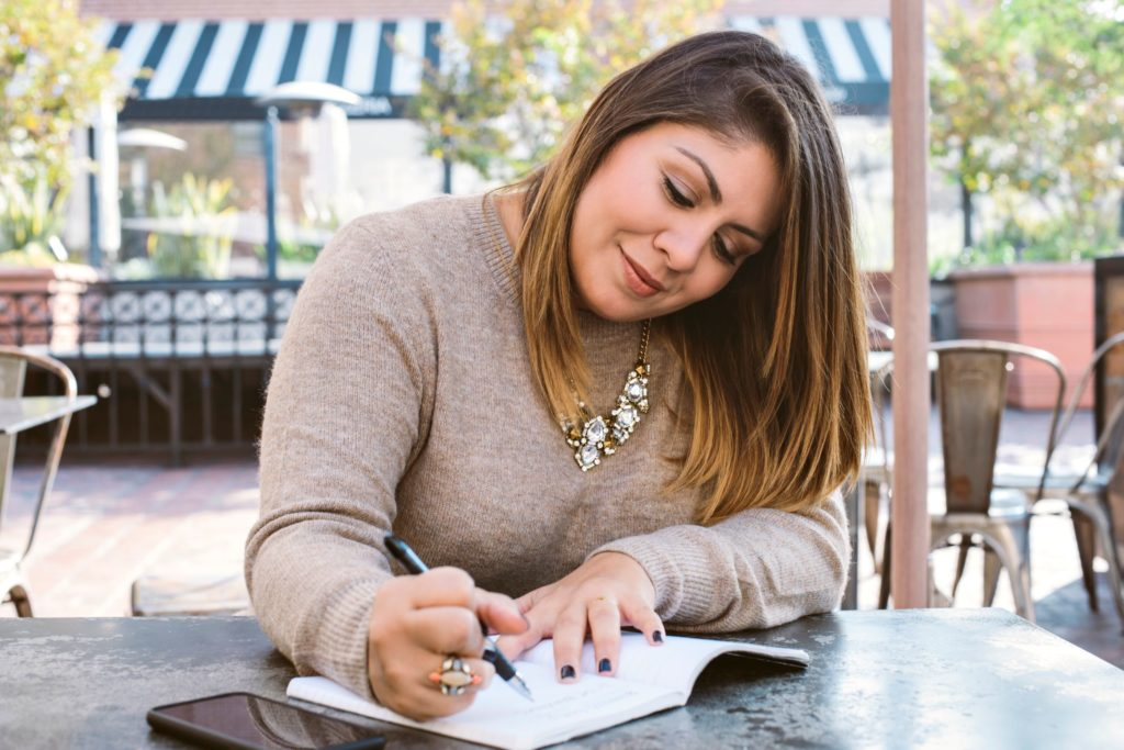 woman writing goals in journal
