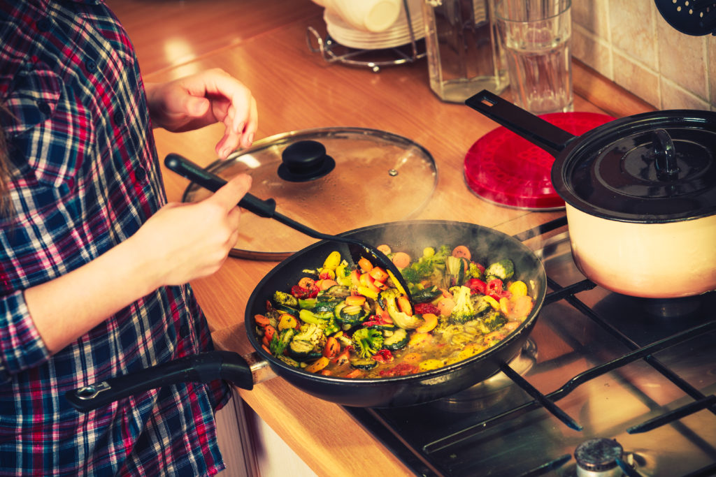 person sauteing vegetables