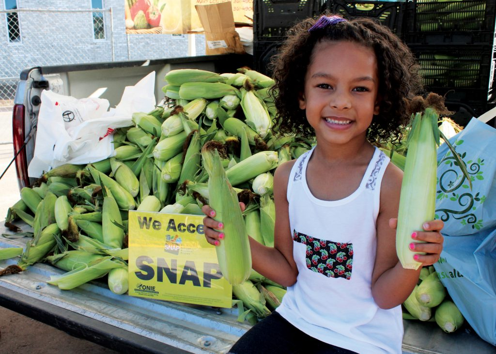 """girl holding corn at the farmers market in front of sign that reads """"we accept SNAP"""""""